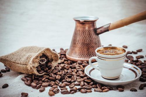 Чашка кофе на фоне турки и кофейных зерен