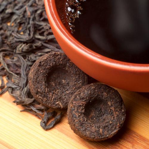 Чашка свежезаваренного чая пуэр и пара То Ча