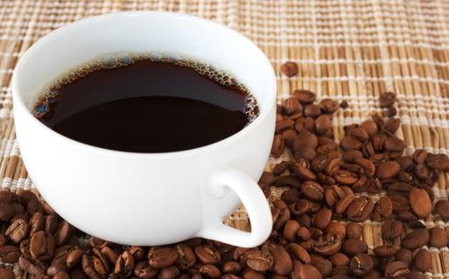 Чашка свежезаваренного эспрессо на фоне кофейных зерен