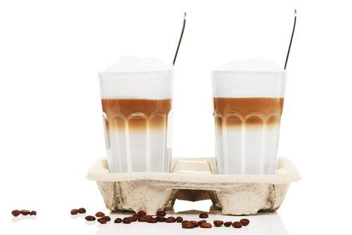 Свежеприготовленный латте макиато на фоне кофейных зерен