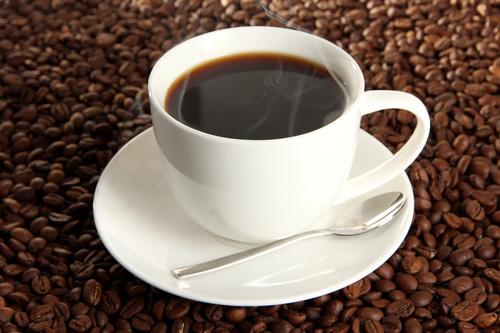Чашка крепкого кофе на фоне кофейных зерен