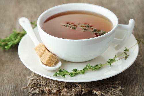 Кружка заваренного чая с чабрецом и тростниковым сахаром
