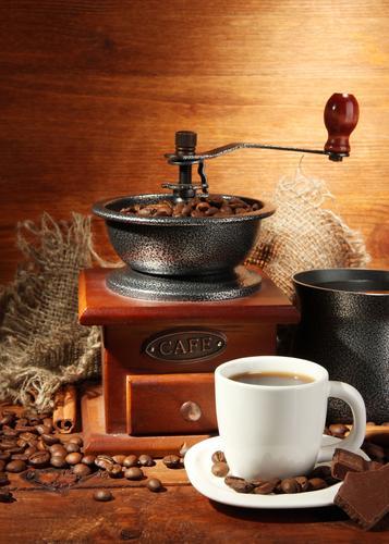 Ручная кофемолка, зерна и кружка свежезаваренного кофе