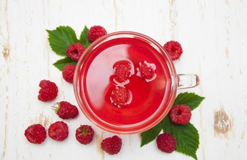 Малиновый чай на фоне свежих ягод и листьев малины