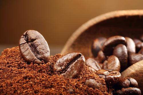 Молотый кофе на фоне кофейных зерен