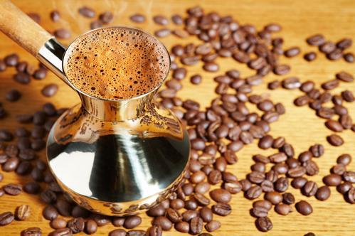 Кофе с пенкой в турке на фоне кофейных зерен