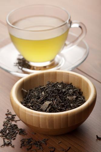 Чашка заваренного чая улун и сухие листья для заваривания