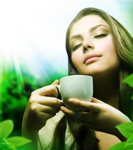 Чашка зеленого чая в руках красивой женщины