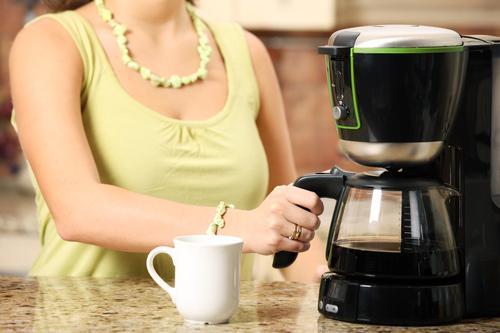 Девушка заваривает кофе в кофемашине