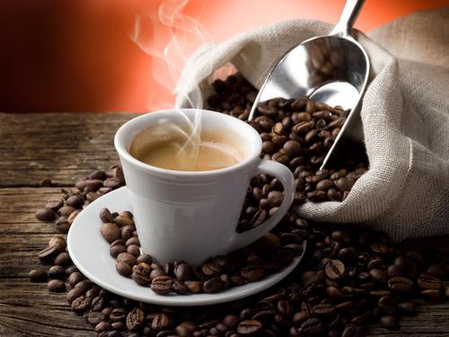 Мешок с кофейными зернами и ароматный горячий кофе на столе