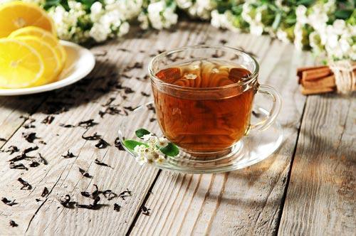Чашка черного чая на деревянном столе