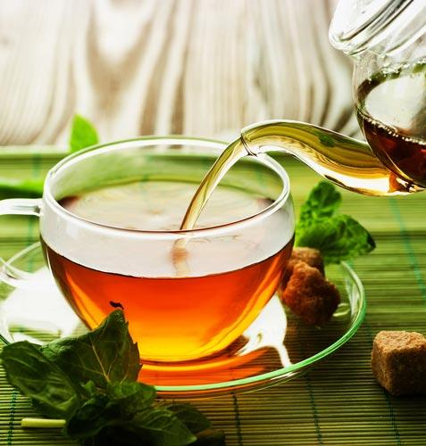 Из чайника в чашку льется ароматный чай