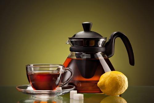 Чай в прозрачном чайнике и чашках с лимоном и сахаром