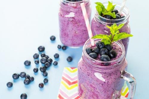 Готовый смузи с черникой, украшенный свежими ягодами и мятой