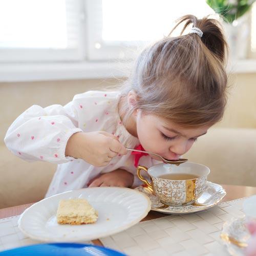 Ребенок пьет чай за столом