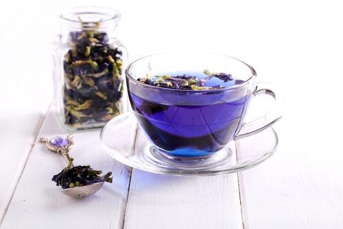 Чашка синего тайского чая и сушеные цветки клитории