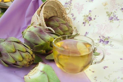 Светло зеленый чай из артишока рядом с бутоном растения