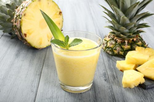 Напиток из ананаса на фоне свежего фрукта