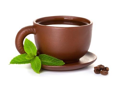 Чашка кофе с листиками ароматной пряности на блюдце