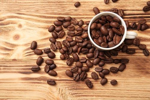 Россыпь кофейных зерен на деревянной поверхности