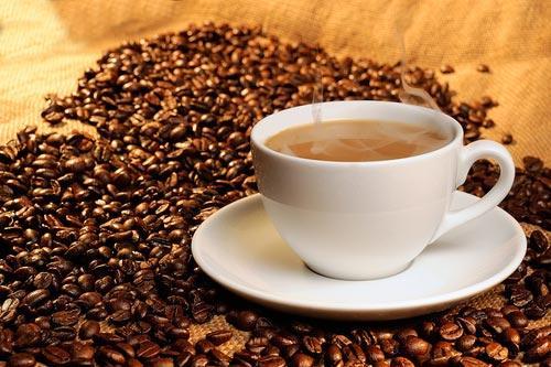 Чашечка кофе на деревянном столе на фоне зерен