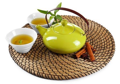 Эмалированный чайник в зеленом цвете на бамбуковом подносе