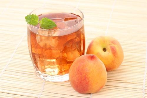 В прозрачном стакане чай из персиков со льдом